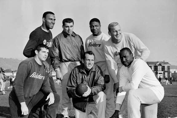 Coach and general manager Al Davis of the Oakland Raiders poses today December 17, 1963 in Oakland, Calif. on practice field with six of his players who have been named to the Associated Press 1963 All-Star team of the American Football League. From left: defensive halfback Tommy Morrow and Fred Williamson, linebacker Archie Matsos, halfback Clem Daniels, center Jim Otto and end Art Powell. (AP Photo/Robert Klein)