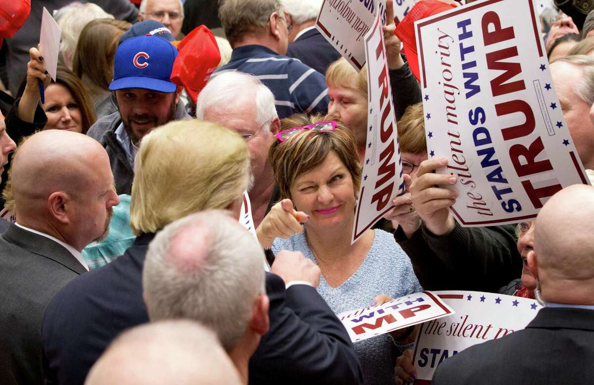 A supporter winks at Republican presidential candidate Donald Trump after he signed an autograph for her during a campaign event at the Roundhouse Gymnasium, Tuesday, Jan. 26, 2016, in Marshalltown, Iowa.