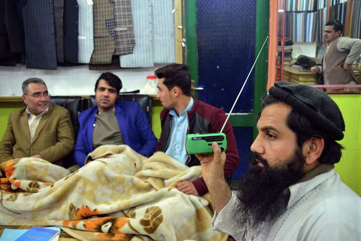 In this photo taken on Sunday, Jan. 10, 2016, an Afghan shopkeeper, right, listens to Islamic State Radio at his shop in Jalalabad, capital of Nangarhar province, Afghanistan.  The Islamic State group in Afghanistan has adopted the media strategy of its mother organization in Syria and Iraq.