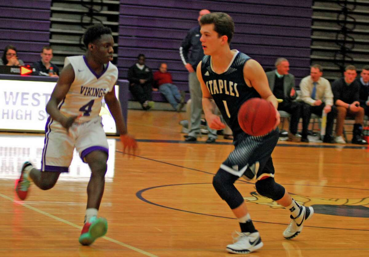 Staples' Justin Seideman, right, tries to move past Westhill's Tank Rivers during a boys basketball game on Tuesday, January 26th 2016.