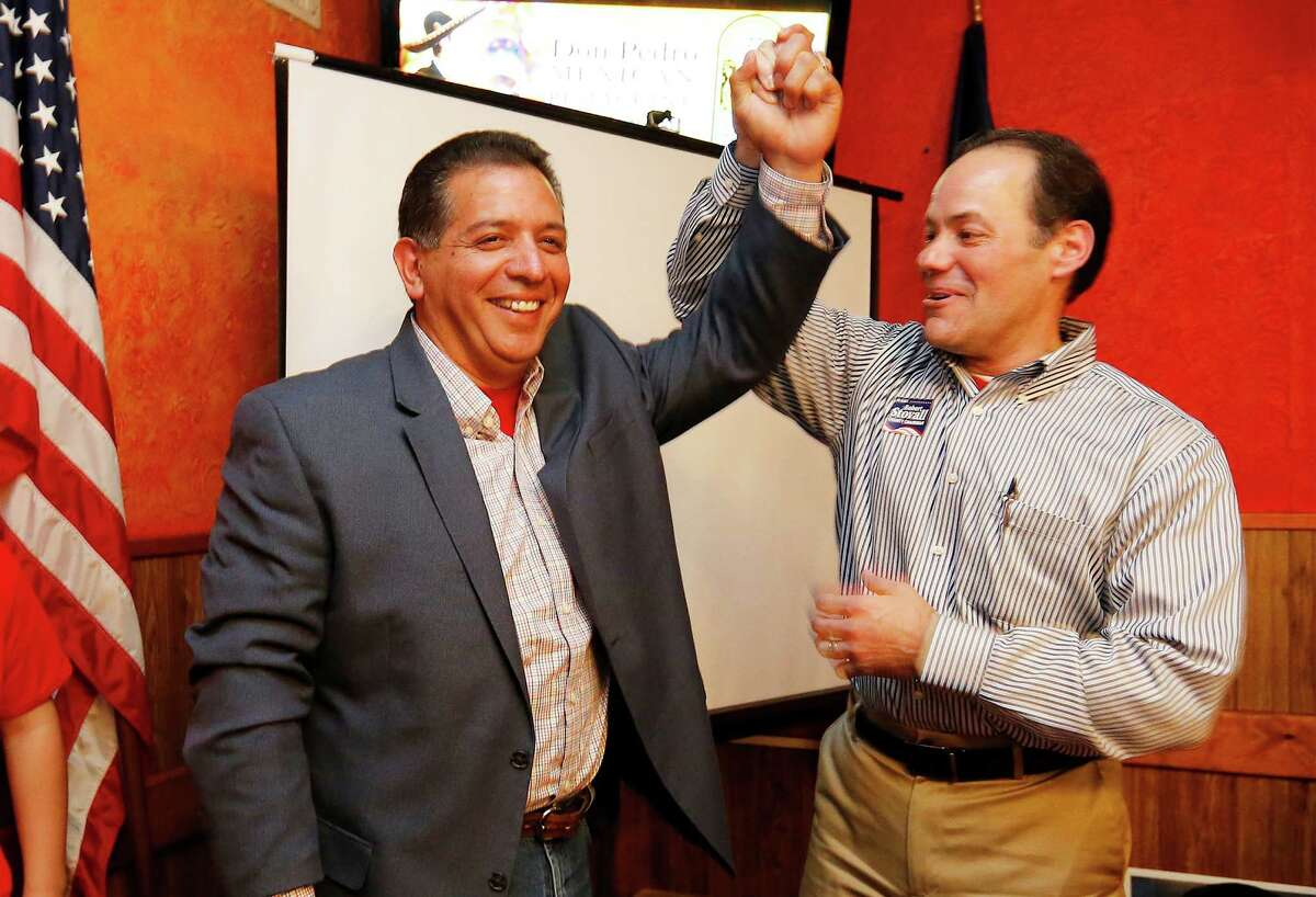 Republican candidate John Lujan (center) and Bexar County GOP Chairman Robert Stovall (right) raise arms in victory at Lujan's election watch party at Don Pedro Mexican Restaurant on Tuesday, Jan. 26, 2016. Lujan was running against Democrat Tomas Uresti in the special runoff election for Texas House District 118. Lujan will replace former state rep. Joe Farias. (Kin Man Hui/San Antonio Express-News)