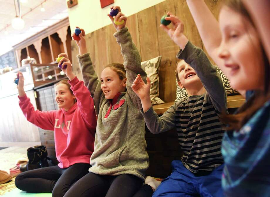 Old Greenwich children, from left, Paloma Pita, 11; Emma Viviano, 11; Téo Pita, 6, and Clara Pita, 7, shake their shakers along to music performed by Joanna Levine during Joannas 'n Bananas Snack 'n Sing at Sweet Pea's Baking Company in Old Greenwich on Monday. , Jan. 25, 2016. Joannas 'n Bananas is an interactive sing-a-long for children, typically up to age four, that fosters musical creativity and expression. The show debuted at Sweet Pea's Monday and will be held every Monday at 4 p.m. Photo: Tyler Sizemore / Hearst Connecticut Media / Greenwich Time
