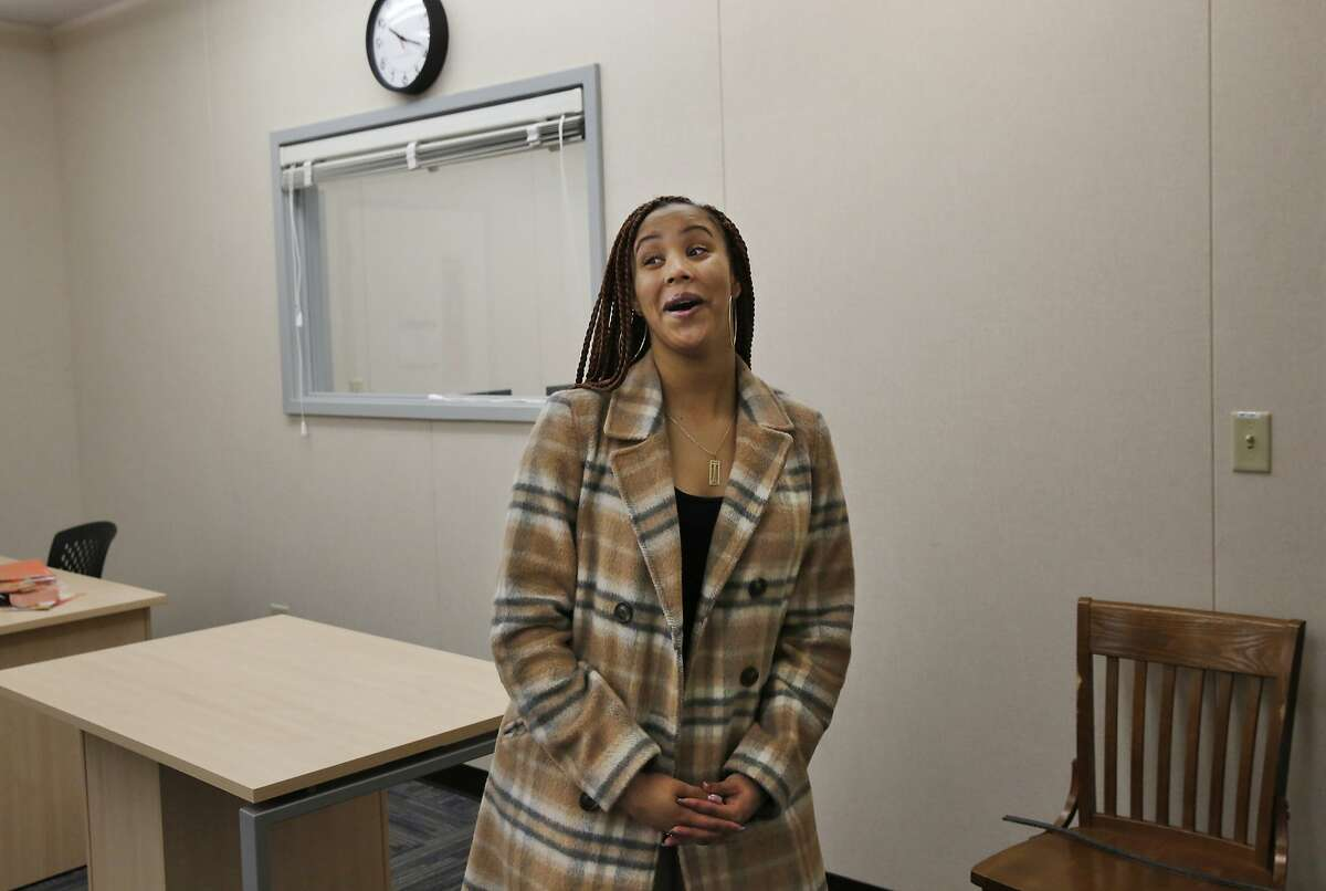Tia Dunbar, 18, takes a look around on a mini-tour from Corey Hill, the College and Career Readiness Specialist as she is filmed by Melhik Hailu of ONews for a feature on Dunbar at Oakland High School's brand new Future Center Jan. 26, 2016 in Oakland, Calif. The Center is part of the Oakland Promise Initiative, which is striving to double the number of college graduates in the city within the next eight years.