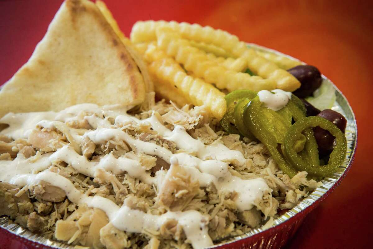 Chicken over rice plate, with extra jalapeé±o and olives and a side of fries, is shown at The Halal Guys at 3821 Farnham on Monday, Jan. 25, 2016, in Houston. The franchise of a famous New York City eatery where people line up for gyros and chicken covered in a secret sauce. ( Brett Coomer / Houston Chronicle )