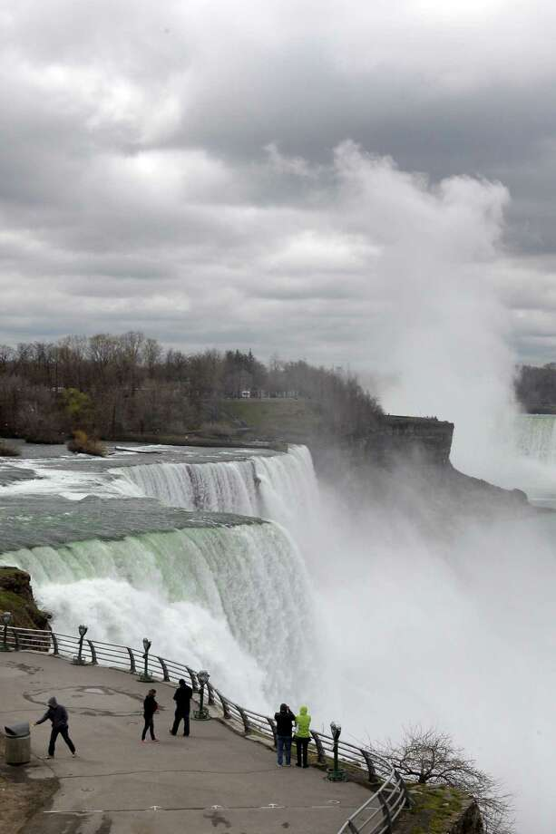 FILE--In this April 11, 2012 file photo, tourists visit the American Falls in Niagara Falls, N.Y. New York officials are considering temporarily turning Niagara Falls into a trickle. State officials are holding a public hearing this week to discuss plans for replacing 115-year-old bridges linking the mainland to islands near the brink of Niagara Falls. To do so, they might reduce the flow on the American side of the falls by building a temporary structure to redirect Niagara River water to the Canadian side. (AP Photo/David Duprey, File) ORG XMIT: NYMG103 Photo: David Duprey / AP