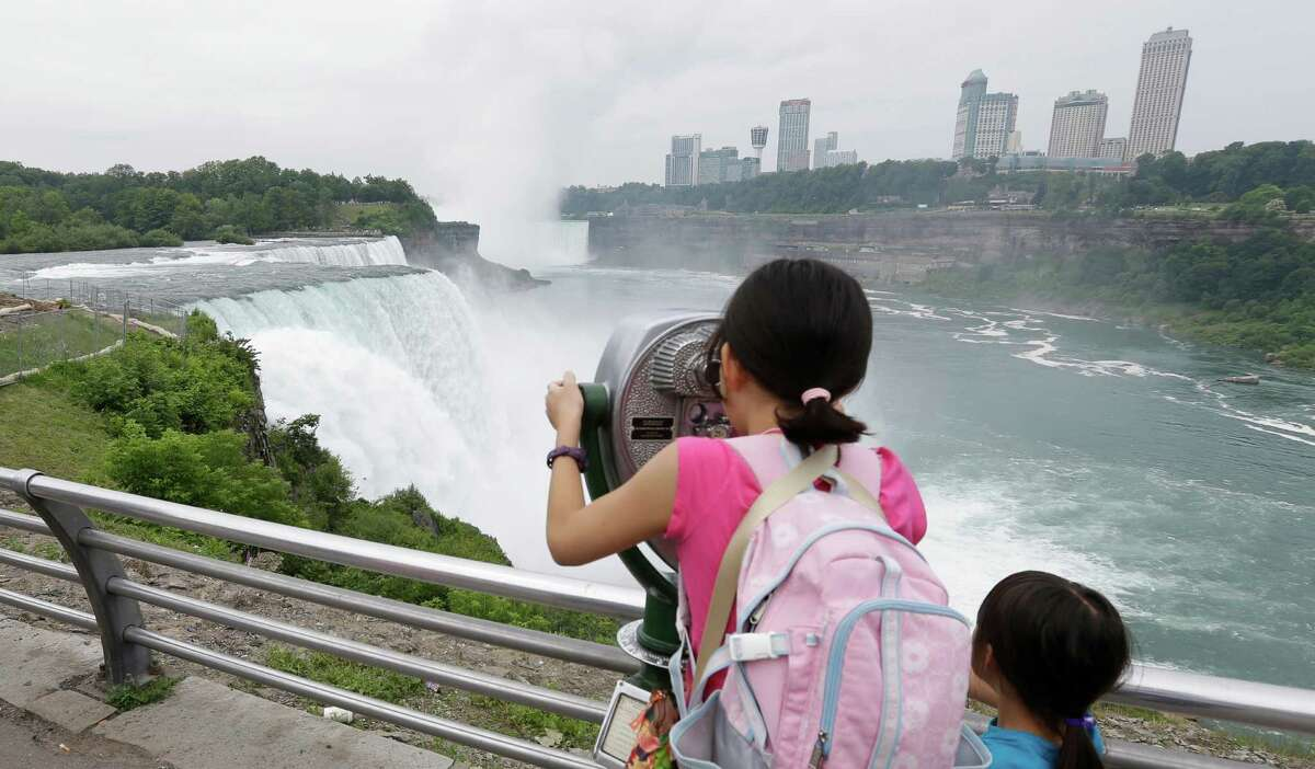 FILE--In this Tuesday, July 2, 2013, file photo, people look at the American Falls in Niagara Falls, N.Y. New York officials are considering temporarily turning Niagara Falls into a trickle. State officials are holding a public hearing this week to discuss plans for replacing 115-year-old bridges linking the mainland to islands near the brink of Niagara Falls. To do so, they might reduce the flow on the American side of the falls by building a temporary structure to redirect Niagara River water to the Canadian side. (AP Photo/David Duprey, File) ORG XMIT: NYMG102