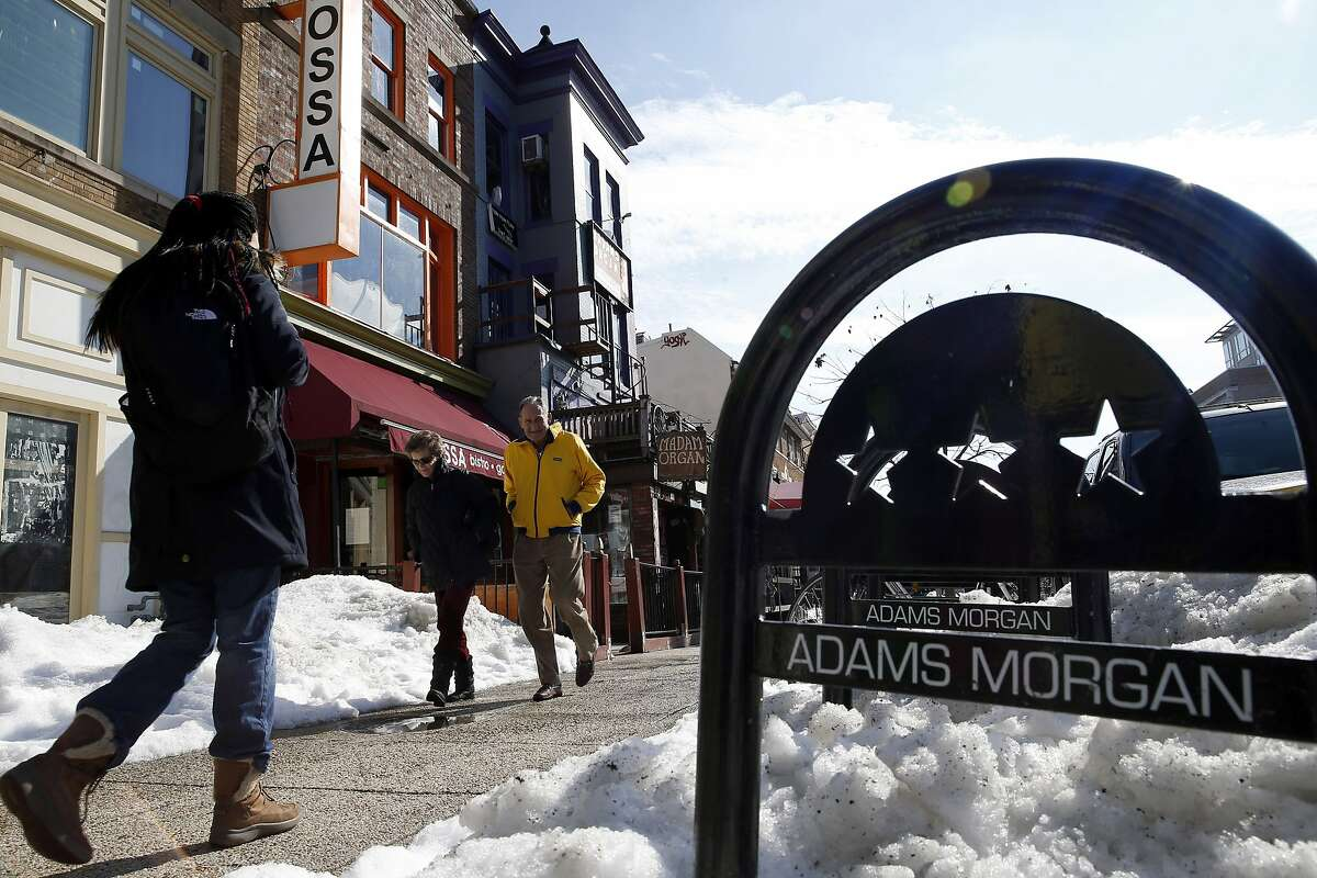 Pedestrians walk past the shops and restaurants on 18th Street NW, Wednesday, Jan. 27, 2016 in the Adams Morgan area of Washington. Residents of Adams Morgan enjoy a bevy of bars, restaurants, exercise studios and shopping, just steps from their row houses and condo buildings. Few neighborhoods can match the perks of Adams Morgan in Washington, D.C. - a reality that reflects a broader problem for the U.S. housing market. (AP Photo/Alex Brandon)