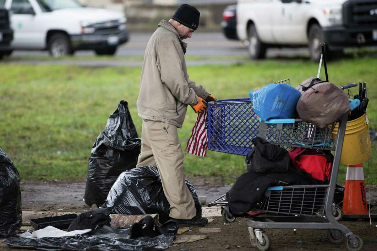 A man tries to attach an American flag to the front of a cart during a clean up of an unsanctioned homeless camp near the Jungle in Sodo on Wednesday, Jan. 27, 2016.