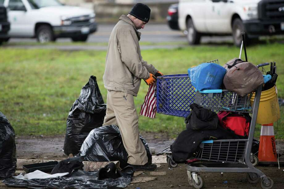 A man tries to attach an American flag to the front of a cart during a clean up of an unsanctioned homeless camp near the Jungle in Sodo on Wednesday, Jan. 27, 2016. Photo: GRANT HINDSLEY, SEATTLEPI.COM / SEATTLEPI.COM
