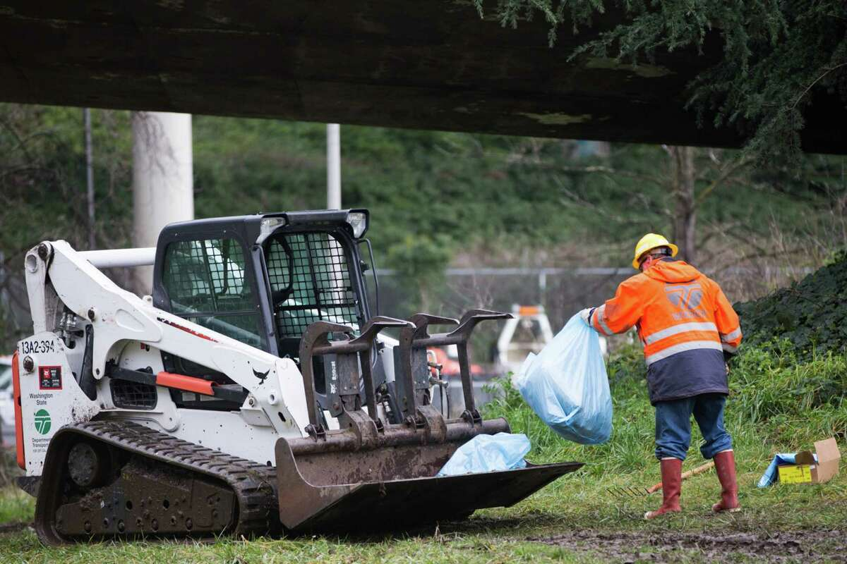 A WSDOT worker loads the front of a skid steer during a clean up of an unsanctioned homeless camp near the Jungle in Sodo on Wednesday, Jan. 27, 2016.