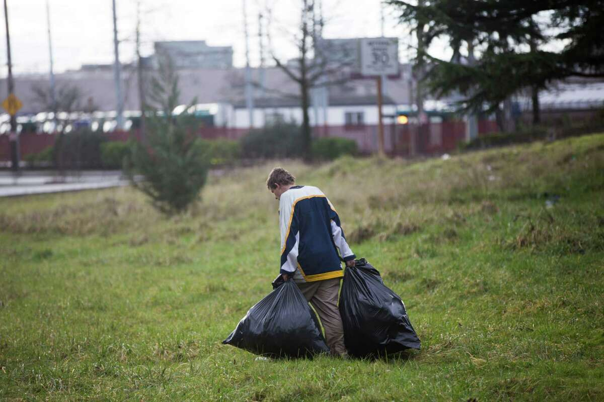 A man drags bags of belongings away during a clean up of an unsanctioned homeless camp near the Jungle in Sodo on Wednesday, Jan. 27, 2016.
