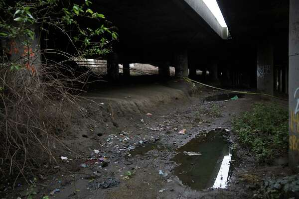"""Police tape is all that's left of police presence the morning after a mass shooting at """"The Jungle,"""" a homeless encampment under Highway 5 in Sodo, on Wednesday, Jan. 27, 2016."""