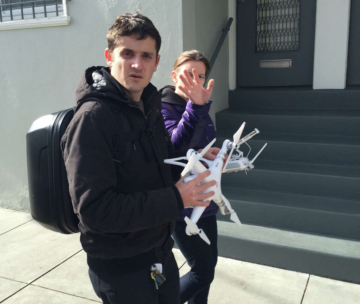 An unidentified drone operator and his friend react negatively to having their picture taken after their device crashed into the Clement Farmer's Market.