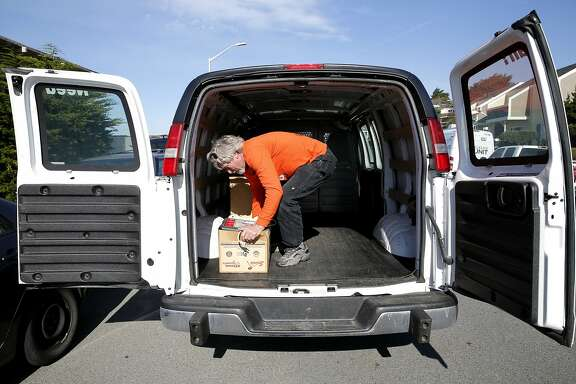 George Neighbors puts a box into a van while moving a friend out of his apartment near an eroding cliff in Pacifica, California, on Wednesday, Jan. 27, 2016.