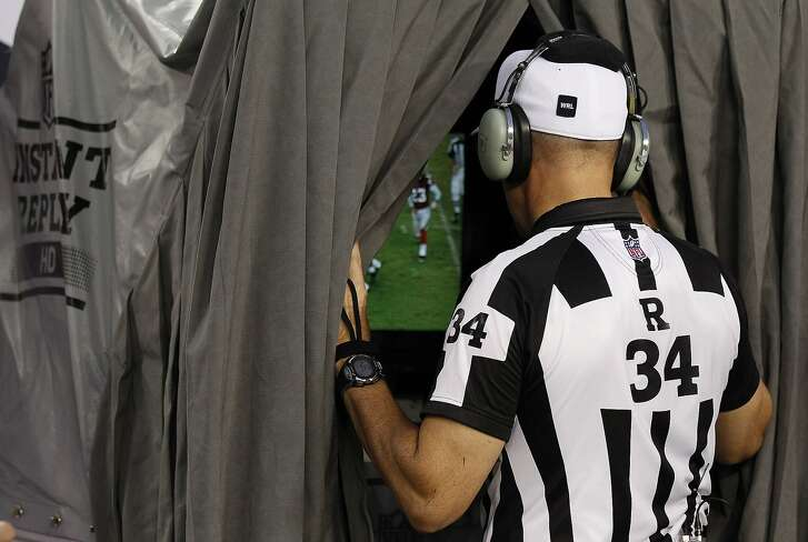 FILE - In this Sept. 25, 2011, file photo, NFL feferee Clete Blakeman looks at replay during a challenge iin an NFL football game between the Tampa Bay Buccaneers and the Atlanta Falcons in Tampa, Fla. Reviewing NFL plays is a high-tech job that's growing in importance now that the NFL reviews every score. It's the job of a small crew at each stadium Sunday to make sure it goes right and goes quickly.  (AP Photo/Chris O'Meara, File)