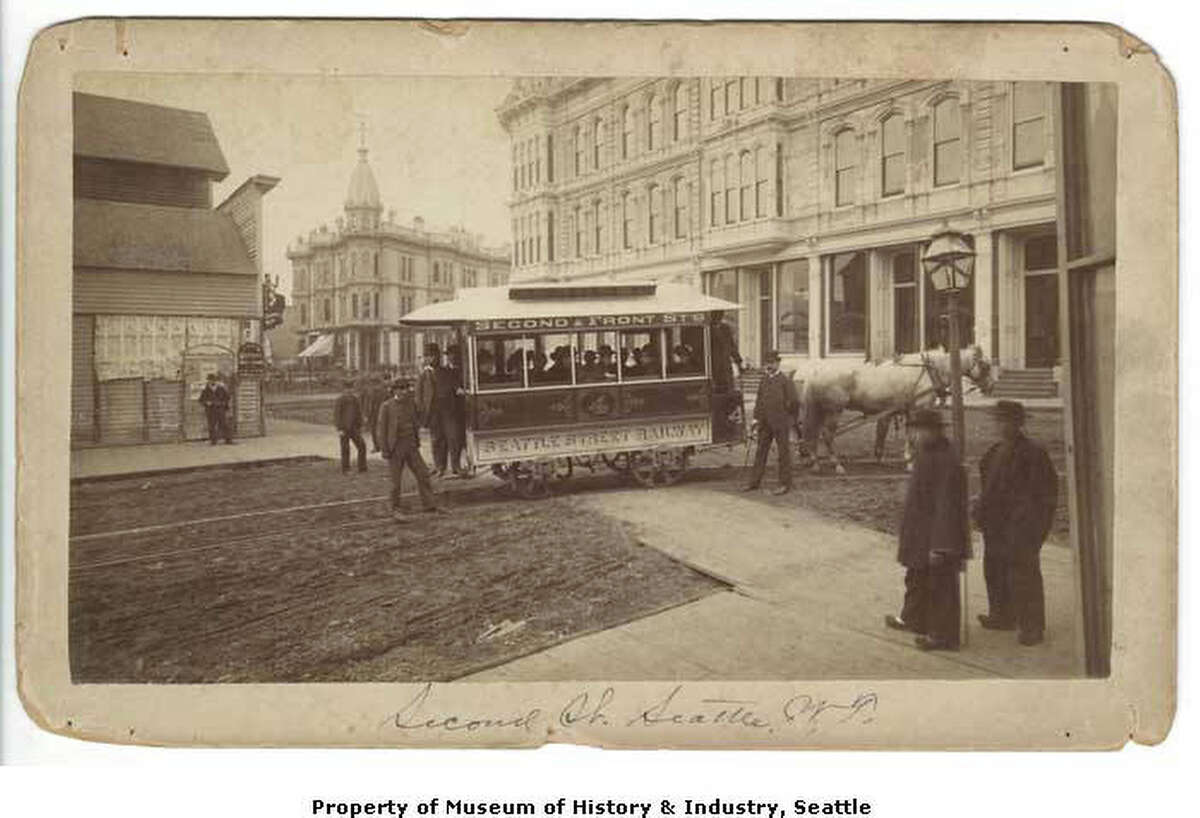 """""""In September 1884, Washington Territory's first streetcar line opened in Seattle. By the end of the year, the line had three miles of track and four streetcars which were operated by a total of 10 men and 20 horses. One branch ran out to Lake Union, and the other ran to Front Street (First Avenue) and on to Queen Anne Hill. The horses that pulled the cars were stabled at the corner of Second Avenue and Pike Street. This photo was taken on the September 1884 opening day of the Seattle Street Railway. Mayor John Leary and invited guests are seated in the horse-drawn streetcar at the intersection of Mill Street (Yesler Way) and Second Avenue. The tracks run through the dirt streets. Two Chinese pedestrians look on from the wooden sidewalk (right)."""" -MOHAI. Photo courtesy MOHAI, Theodore E. Peiser photo, Seattle Historical Society Collection, image number shs898."""