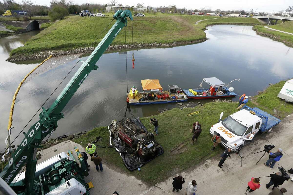 The first of four vehicles was removed from Brays Bayou at Old Spanish Trail in Houston on Wednesday. Harris County, the Houston Police Department and city of Houston are cooperating in the effort.