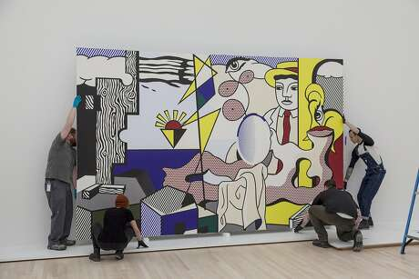 "Installation crew hangs Roy Lichtenstein's ""Figures with Sunset"" at the San Francisco Museum of Modern Art."