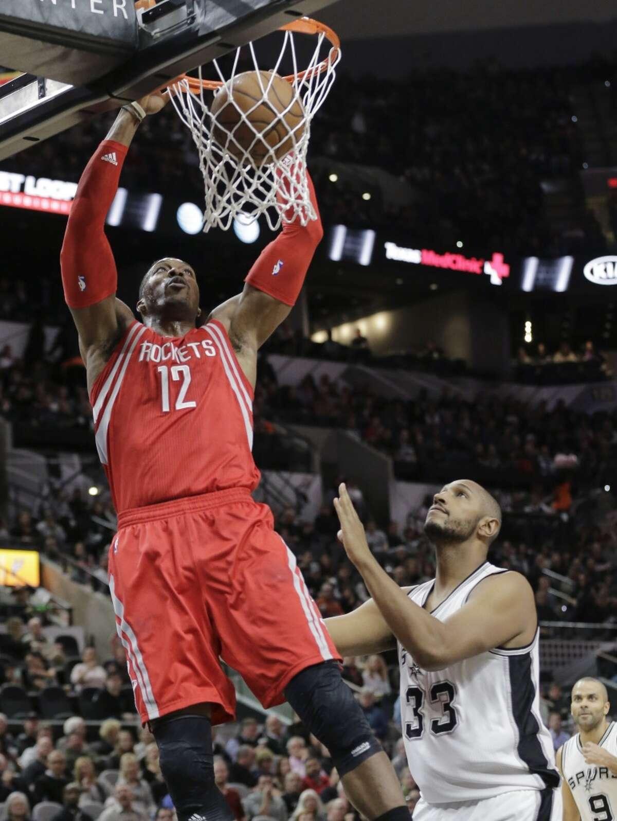 Houston Rockets center Dwight Howard (12) scores over San Antonio Spurs center Boris Diaw (33) during the first half of an NBA basketball game, Wednesday, Jan. 27, 2016, in San Antonio. (AP Photo/Eric Gay)