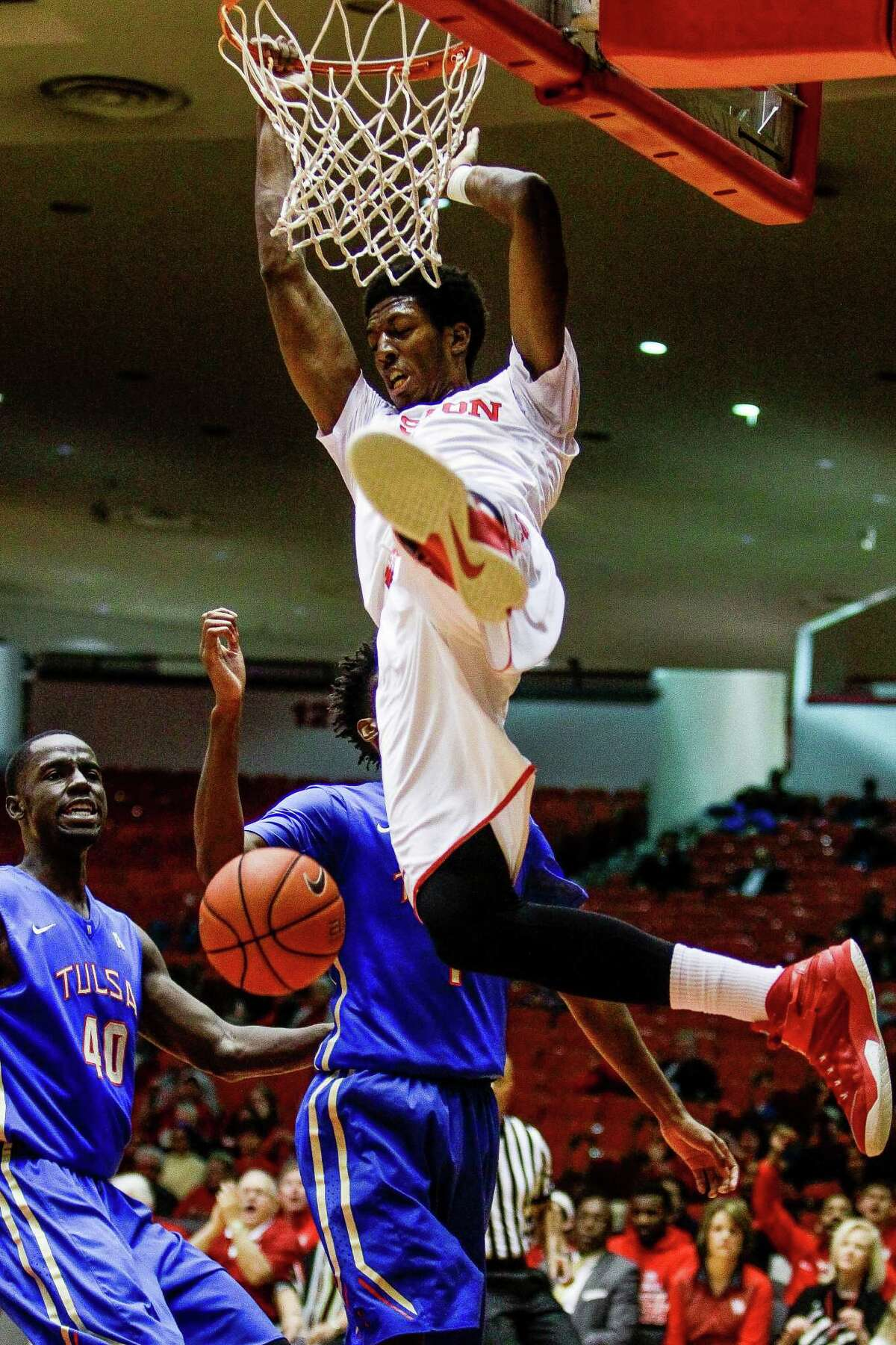 Houston Cougars forward Danrad Knowles (0) swings off the hoop after a dunk as the Houston Cougars take on the Tulsa Golden Hurricane at Hoffheinz Pavillion Wednesday, Jan. 27, 2016, in Houston.