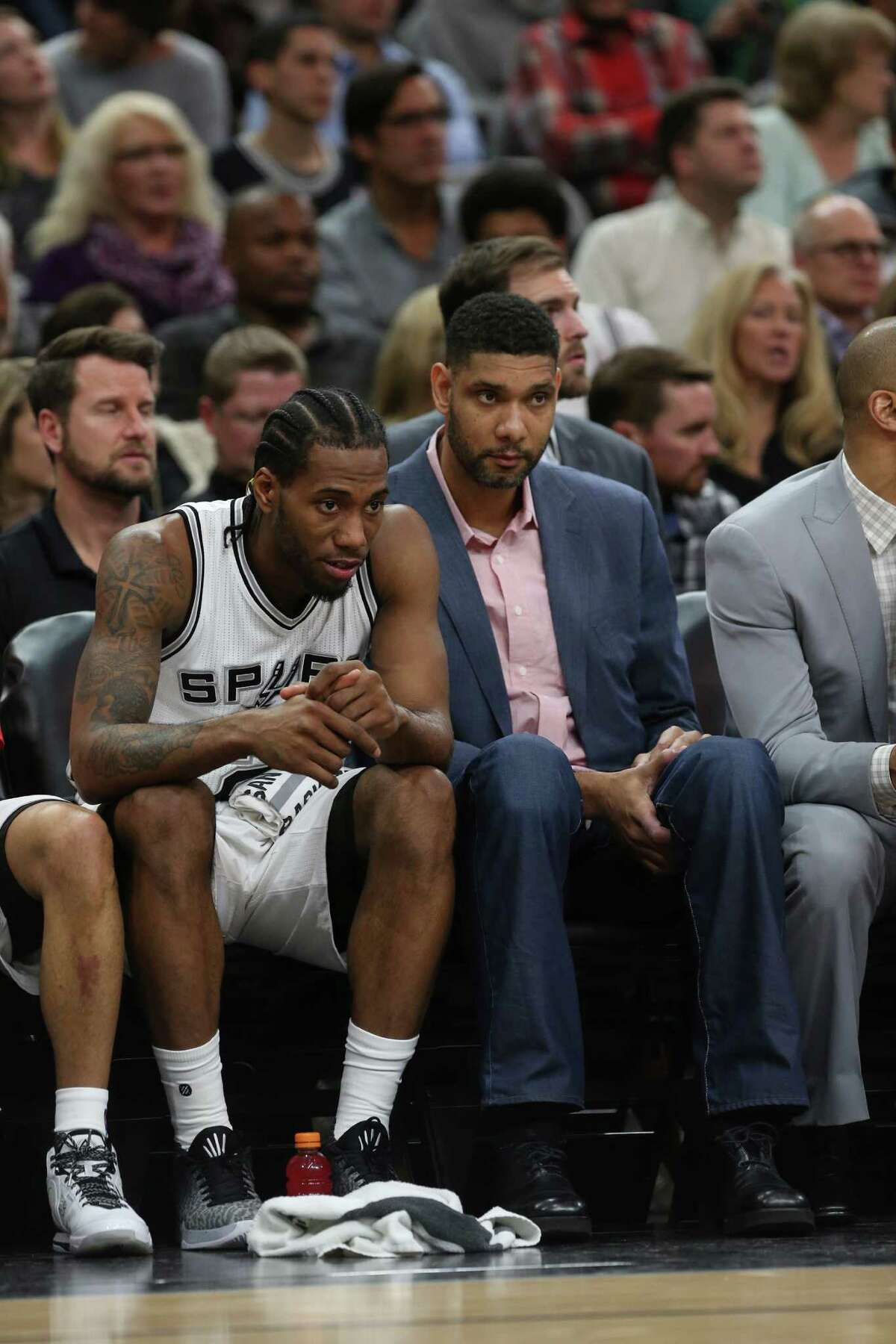 Spurs' Tim Duncan sits with Kawhi Leonard during the first half against the Houston Rockets at the AT&T Center on Jan. 27, 2016.
