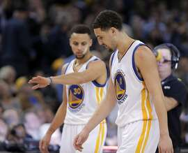 Stephen Curry (30) reaches out to high five Klay Thompson (11) after Thompson hit a three pointer in the second half as the Golden State Warriors played the Dallas Mavericks at Oracle Arena in Oakland, Calif., on Wednesday, January 27, 2016.