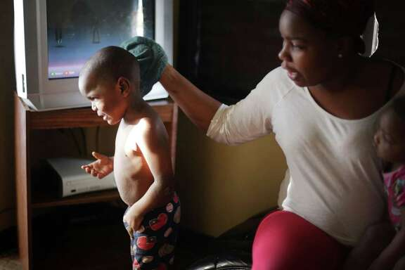 Ariana Hawk, 25, is the single mother of three children under the age of ten living in Flint, Mich., with her mother. She bathes her middle child Sincere Smith, 2, who is unable to bathe with tap water. He is suffering from a breakouts all over his body that his mother believes are a reaction to the contaminated water. She must use bottled water to wash him daily. (Regina H. Boone/Detroit Free Press/TNS)