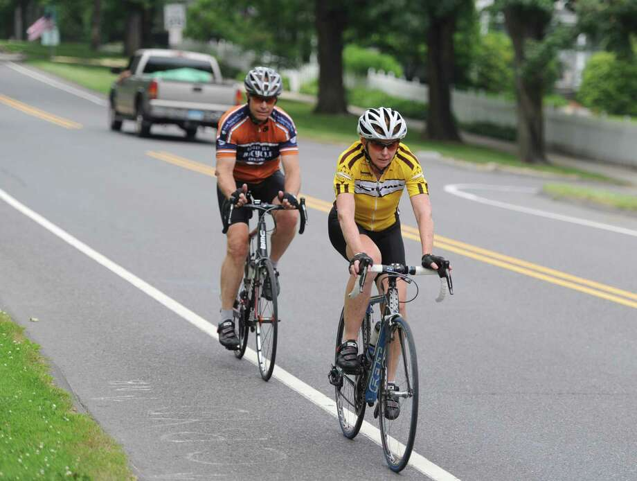 Cyclists ride their bicycles along along Main Street in Ridgefield, Conn. Thursday, July 3, 2014. Bike Walk Connecticut released a first-of-its-kind ranking of Connecticut's towns' bike- and walk-friendliness. Ridgefield ranked near the top at 14th overall. Photo: Tyler Sizemore / Tyler Sizemore / The News-Times