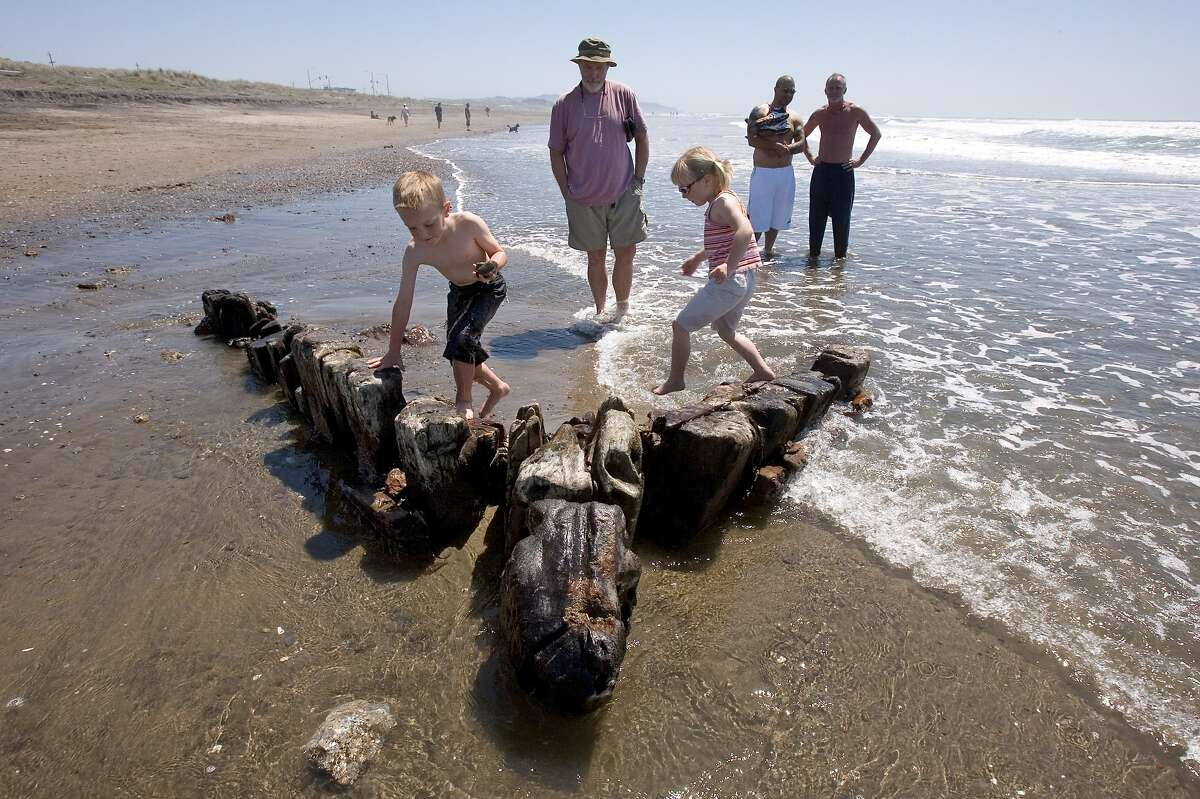 The King Philip shipwreck, a wrecked 19th century clipper ship that has recently surfaced on Ocean Beach in San Francisco,can been seen a low tides if the sand has shifted off of the wreck.
