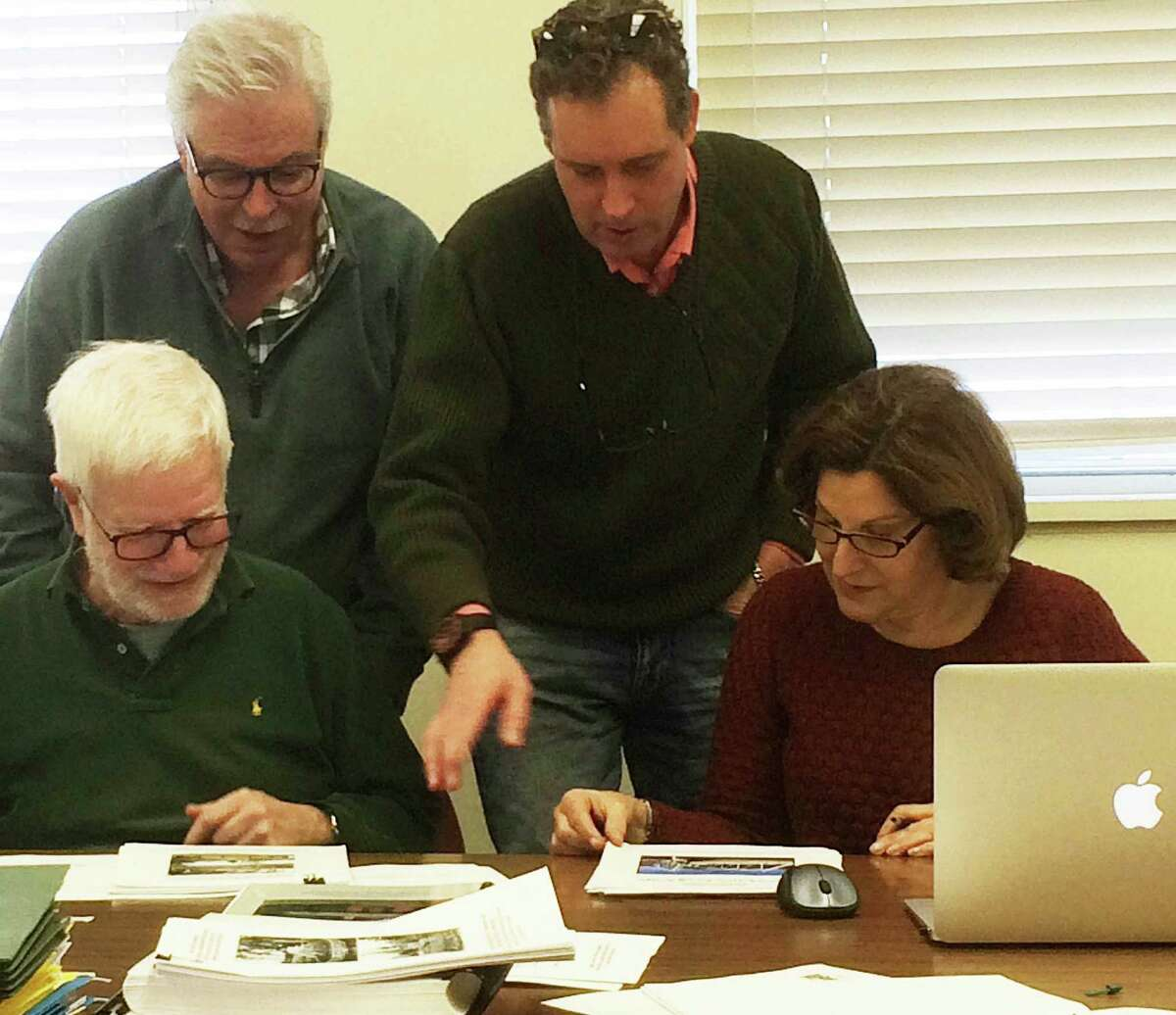 Members of the Saugatuck Swing Bridge Study Subcommittee -- Robert Weingarten, Peter Fullbright, Morley Boyd and Janet Rubel look at pictures of the span -- met to discuss finishing touches on their report that wiill recommend designating the span a local historic landmark.