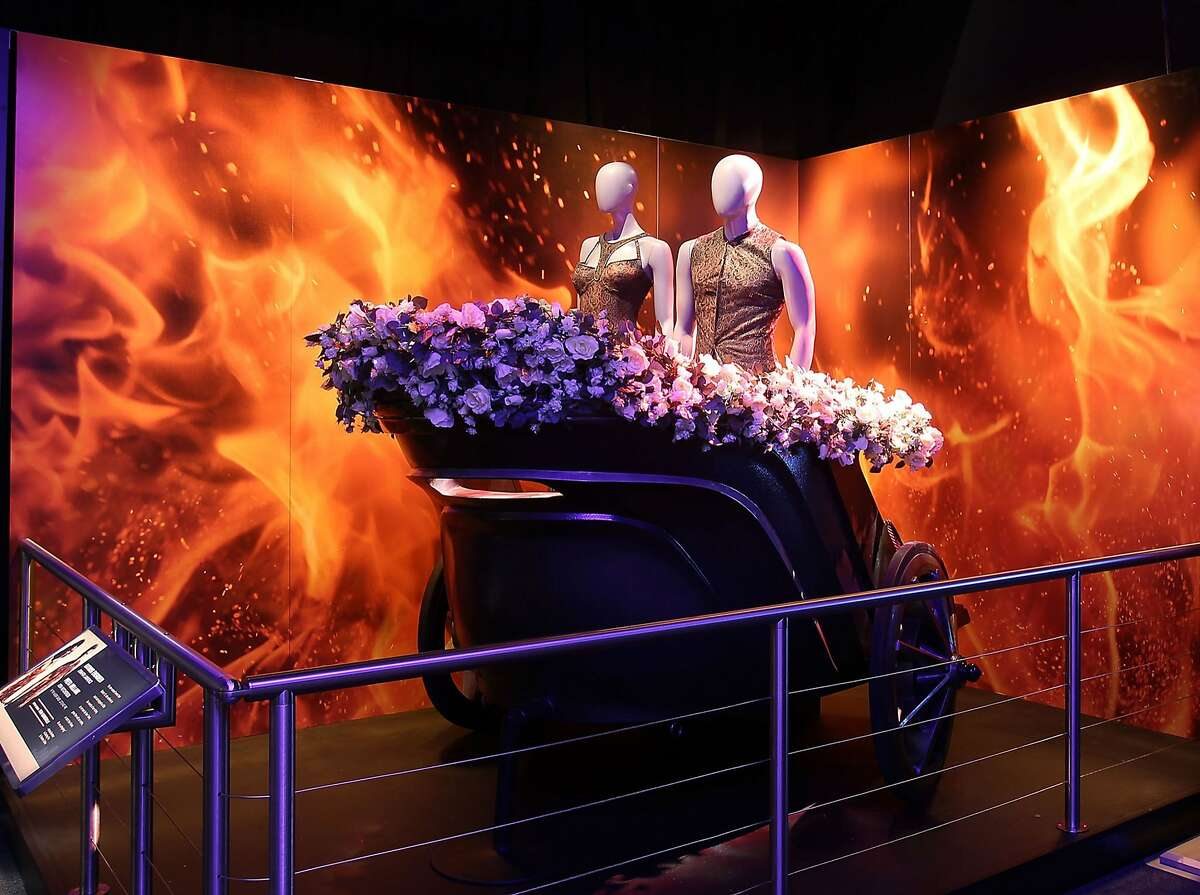 """Katniss Everdeen and Peeta Mellark ride a chariot in the tributes parade in """"The Hunger Games: Catching Fire,"""" part of The Hunger Games: The Exhibition, opening Saturday, February 13, at the Innovation Hangar, Palace of Fine Arts, San Francisco. Photo courtesy of Hunger Games: The Exhibition."""