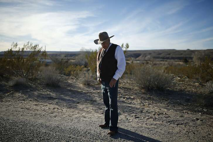 Rancher Cliven Bundy stands along the road near his ranch after talking to media Wednesday, Jan. 27, 2016, in Bunkerville, Nev. Cliven Bundy and his wife Carol Bundy was returning from a trip to visit the family of LaVoy Finicum, a 55-year-old rancher from Cain Beds, Ariz., who died Tuesday after law enforcement officers initiated a traffic stop near the Malheur National Wildlife Refuge. It's unclear what happened in the moments before his death.