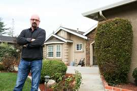 Ronald Roosenboom poses for a photograph in front of the home he rents out in Saratoga, Calif on Thursday, Jan. 28, 2016. Roosenboom feels trapped by his house because if he were to sell it he would owe tax on $1.4 million in profit.