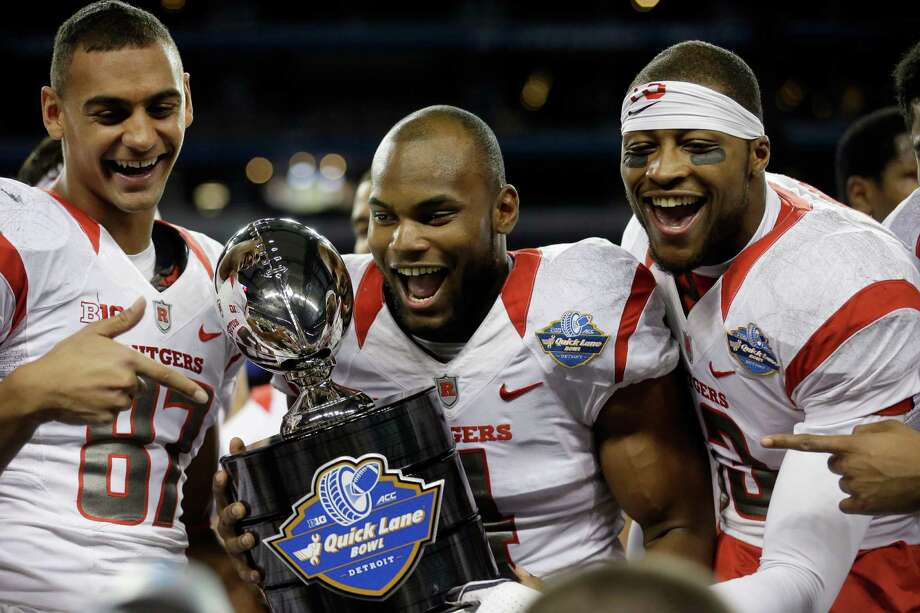 Rutgers wide receivers Vance Matthews (87), Leonte Carroo, center, and Carlton Agudosi flank the trophy after winning the Quick Lane Bowl NCAA college football game against North Carolina, Friday, Dec. 26, 2014, in Detroit. Rutgers defeated North Carolina 40-21. (AP Photo/Carlos Osorio) Photo: Carlos Osorio, Associated Press / AP