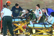 Jeremy Robison watches as his son Raj Robison is wheeled to a waiting ambulance after an alleged carbon monoxide leak at Beaumont's Marshall Middle School began making students ill. Several dozen students and adults were transported to area hospitals from the event.  Photo taken Thursday, January 28, 2016 Guiseppe Barranco/The Enterprise