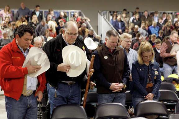 Buyers and spectators took a moment for a prayer Saturday, Feb. 28, 2015 before the start of he San Antonio Stock Show & Rodeo Junior Steer Auction. The grand champion steer, who was shown by Jagger Horn, was auctioned for $130,000.