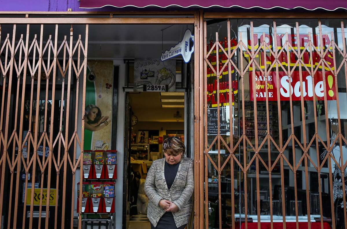 Araceli Espinoza, co-owner of Thalia's Jewelry looks down as she poses for a portrait at the entrance of her store, in San Francisco, California on Thursday, January 28, 2016. Espinoza said it was an emotional day for her, as January 28th marks the one-year anniversary of the fire that destroyed their previous jewelry store.
