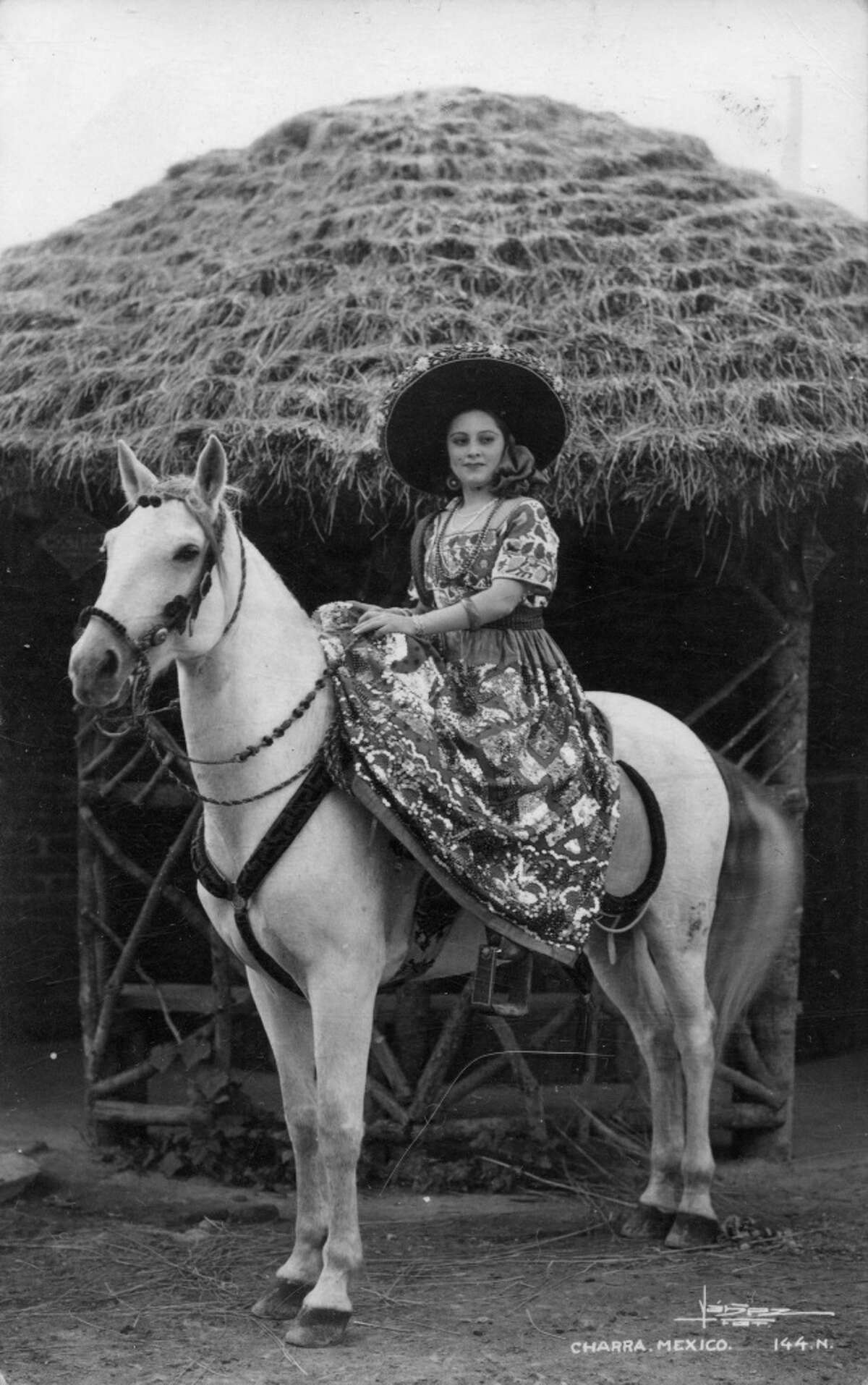 The charra style dates back to the 1800s. Here, a Mexican woman poses in costume and on horseback in the 1940s.