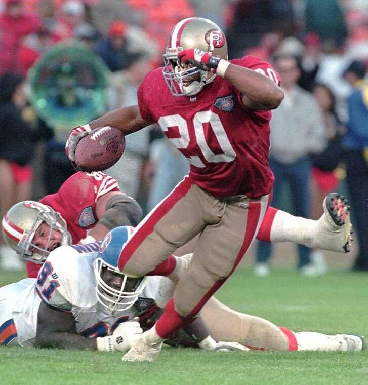 San Francisco 49ers' Derek Loville (20) evades a would-be tackle by Denver Broncos Willie Oshodin (91) during the fourth quarter Friday, Aug. 12, 1994, at Candlestick Park in San Francisco. The 49ers defeated Denver, 20-3. (AP Photo/Ben Margot)