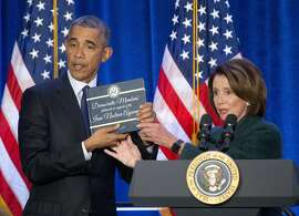President Barack Obama, left, is presented a copy of the Iran Nuclear Agreement Legislation by House Minority Leader Nancy Pelosi of Calif., right, before speaking at the House Democratic Issues Conference in Baltimore, Md., Thursday, Jan. 28, 2016.