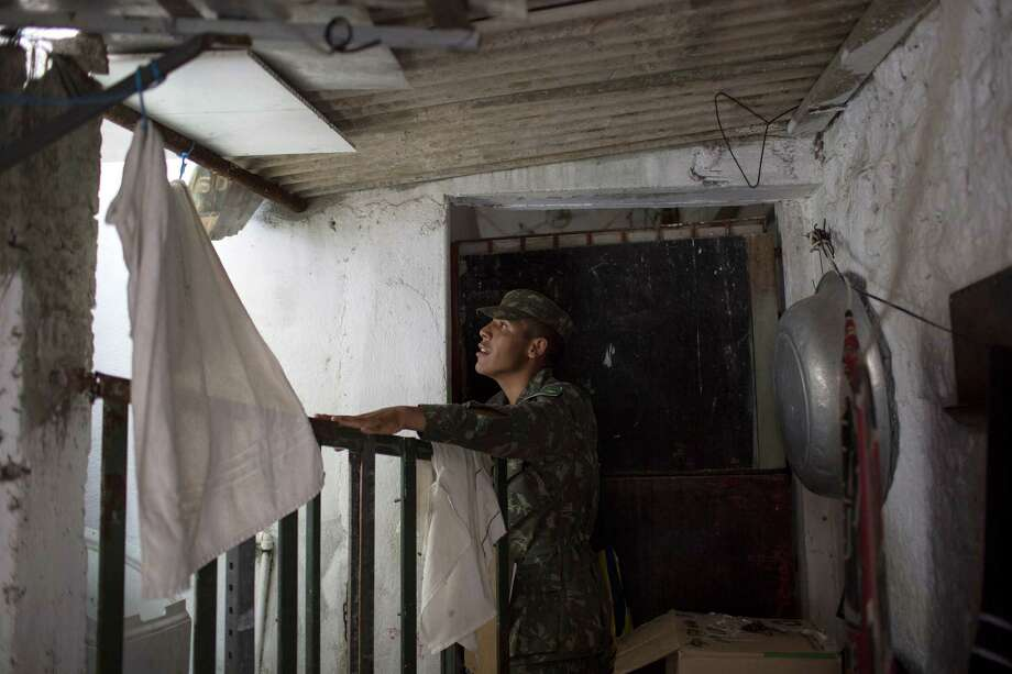 A Brazilian Army soldier inspects a house during an operation to combat the Aedes aegypti mosquitoes that transmits the Zika virus in Recife, Pernambuco state, Brazil, Tuesday, Jan. 26, 2016. Brazil's health minister Marcelo Castro said that nearly 220,000 members of Brazil's Armed Forces would go door-to-door to help in mosquito eradication efforts ahead of the country's Carnival celebrations. (AP Photo/Felipe Dana) ORG XMIT: XFD108 Photo: Felipe Dana / AP