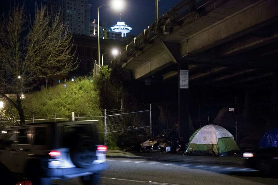 A car zips by a homeless encampment on a sidewalk in Belltown early in the morning on Friday, Jan. 29, 2016. Photo: GRANT HINDSLEY, SEATTLEPI.COM / SEATTLEPI.COM