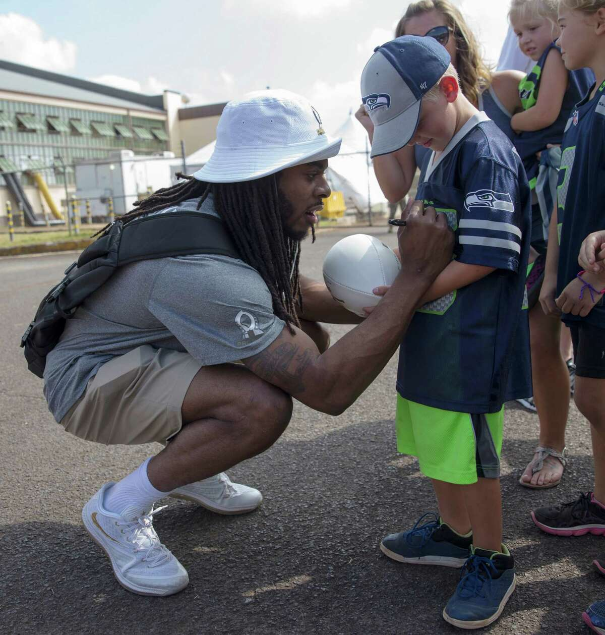 Seattle Seahawks cornerback Richard Sherman signs autographs for a young fan before the NFL football Pro Bowl draft Wednesday, Jan. 27, 2016, at Wheeler Army Airfield in Wahiawa, Hawaii. (AP Photo/Marco Garcia)