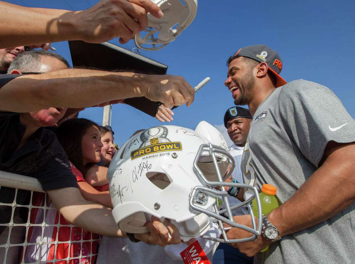 Seattle Seahawks quarterback Russell Wilson, right, signs autographs for his fans during the NFL Pro Bowl Football Draft show at the Wheeler Army Airfield, Wednesday, Jan. 27, 2016, in Wahiawa, Hawaii. (AP Photo/Eugene Tanner)