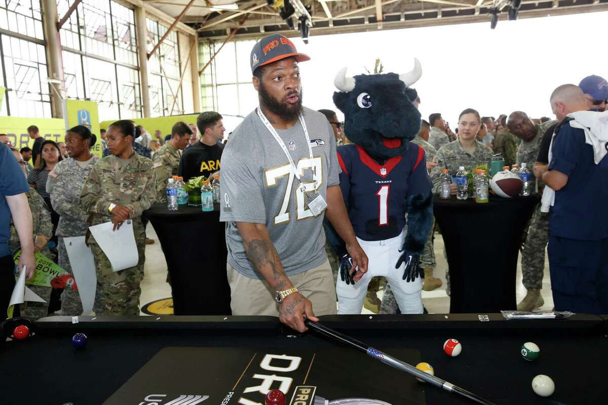 Seattle Seahawks defensive end Michael Bennett (72) plays a game of pool at the NFL Pro Bowl football draft at Wheeler Army Airfield, Wednesday, Jan. 27, 2016, in Wahiawa, Hawaii. (AP Photo/Marco Garcia)