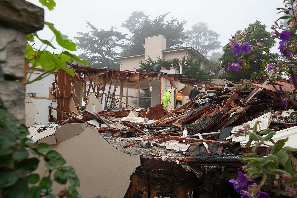 Construction workers demolish the building located at 256 Casitas Ave. in the Mount Davidson area, Friday, Jan. 29, 2016, in San Francisco, Calif. The building, that was purchased just a few months ago, was demolished after it started to slide down the hill.
