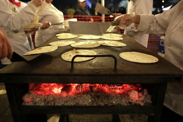 Volunteer cooks heat up tortillas for tacos at the annual Cowboy Breakfast  at Cowboys Dance Hall on Friday, January 29, 2016.