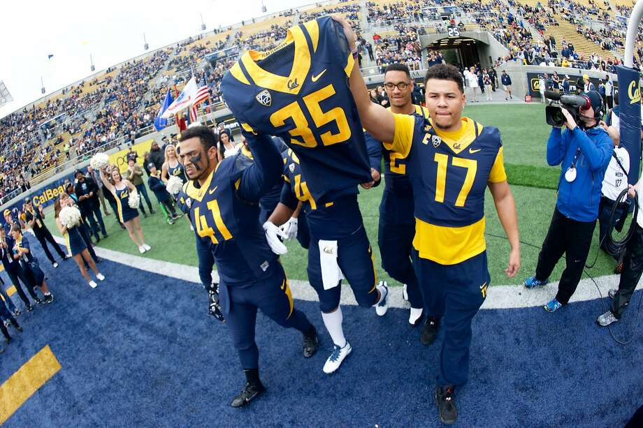 November 29, 2014: California defensive ends Todd Barr (41) and Brennan Scarlett (17) carry the jersey of teammate Ted Agu who died during off-season conditioning before the NCAA football game between the California Golden Bears and the BYU Cougars at Memorial Stadium in Berkeley, CA. Photo: Matt Cohen, AP