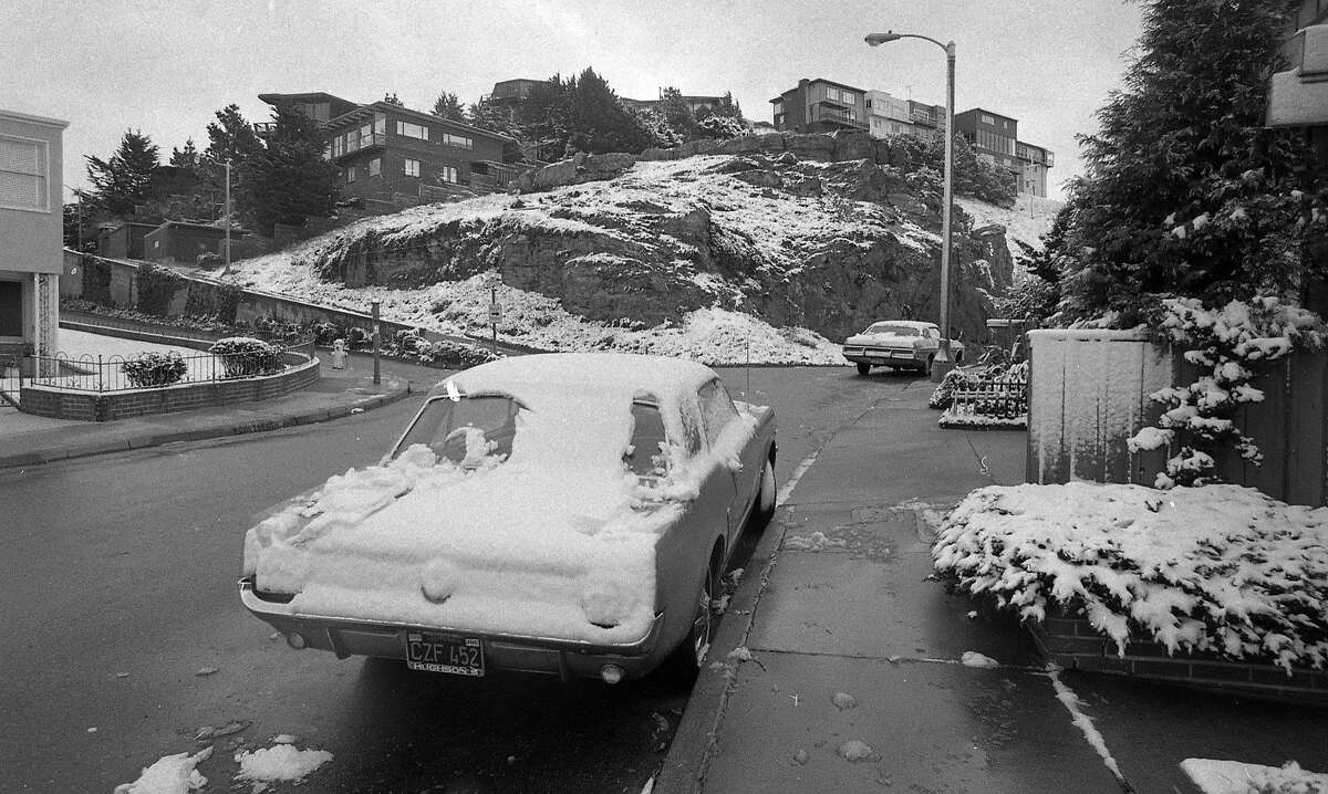 San Francisco snow falls in 1976. A Mustang in the city is covered with powder.