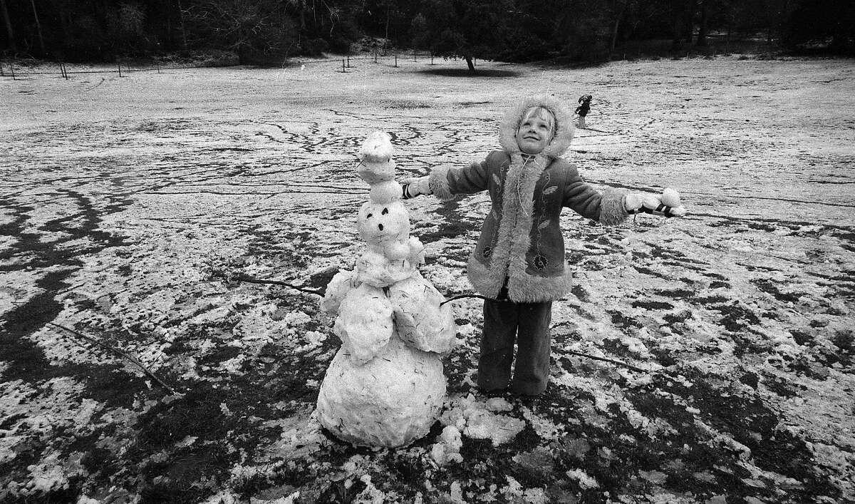 On Feb. 5, 1976, a girl builds a snowman in Golden Gate Park during a rare San Francisco snowfall.